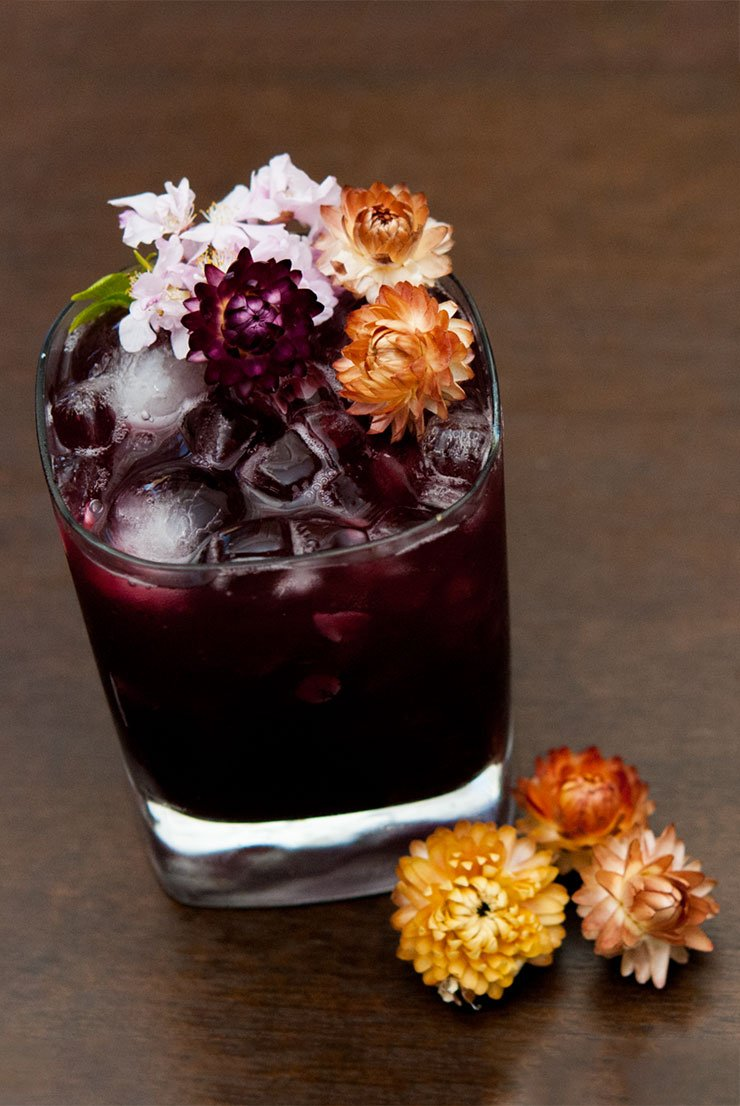 A purple cocktail in a tumbler on a wooden table, garnished with tropical dry and fresh flowers.