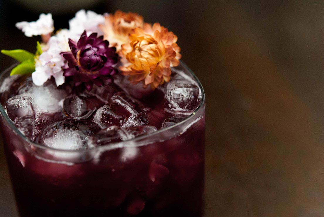 A closeup of a dark purple cocktail on a wooden table, garnished with dry tropical flowers.