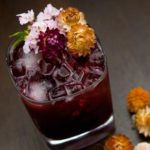 A dark purple cocktail on a wooden table, garnished with dry tropical flowers with a sprinkle of flowers beside it.