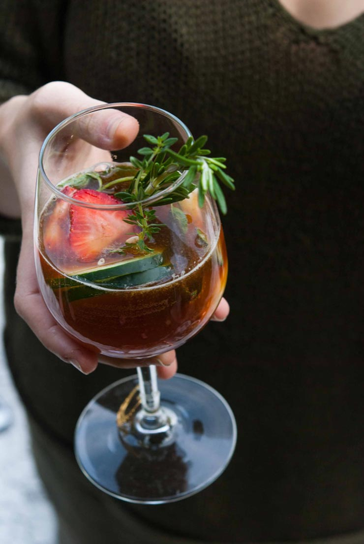a hand holding a Pimm's Cup cocktail in a wine glass, full of herbs, cucumber and fruits.