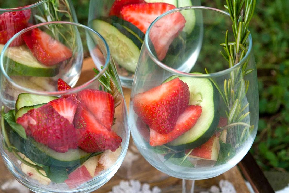 A closeup of 2 wine glasses on a wooden tray full of herbs, fruits and cucumbers..