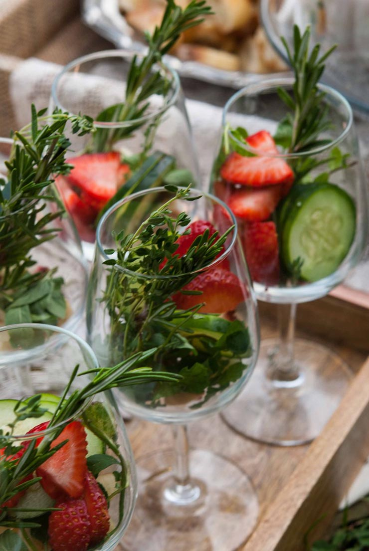 5 wine glasses on a wooden tray full of herbs, fruits and cucumbers.
