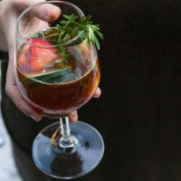 A hand holding a cocktail, garnished with cucumbers, strawberries and rosemary.