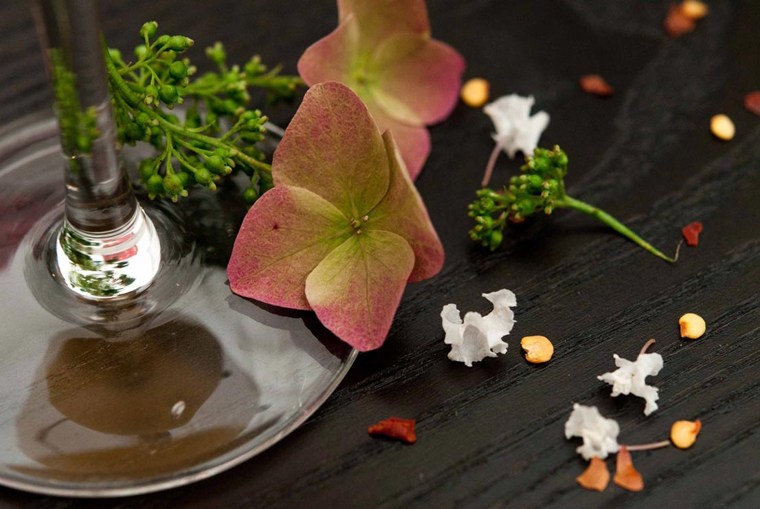 A sprinkling of flowers and greenery at the base of a cocktail on a black table.