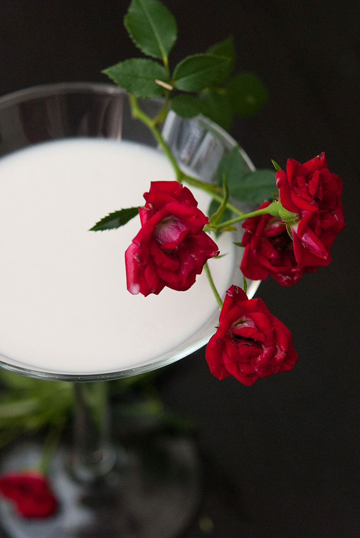 A closeup of a white cocktail in a martini glass garnished with red roses.