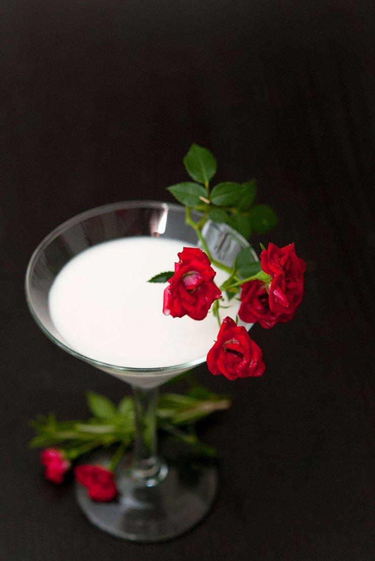 A white cocktail in a martini glass garnished with red roses.
