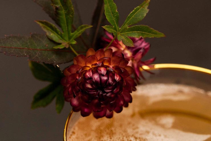 A closeup of dry, purple flowers with green leaves garnishing a cocktail with a gold-rimmed glass.