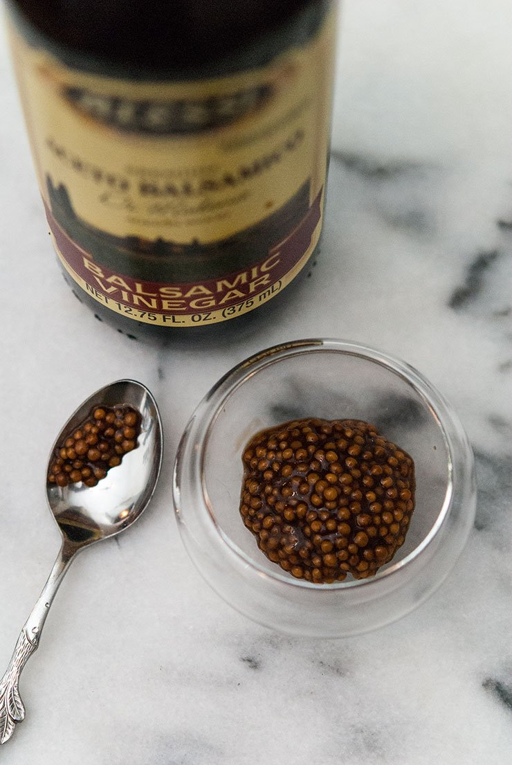 A bottle of balsamic vinegar, a small spoon and and a small bowl of balsamic mustard caviar on a white, marble table.