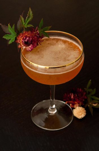 A cocktail garnished with dry flowers and leaves.