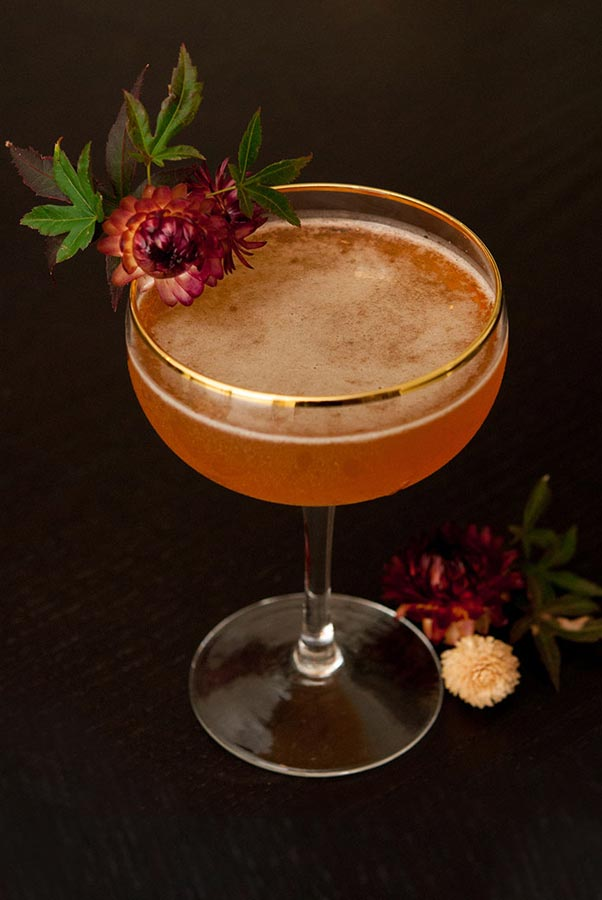 A cocktail garnished with dry flowers and leaves, with a few flowers at its base.
