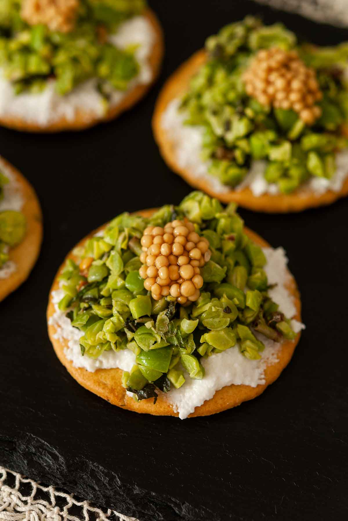 3 spring pea appetizers topped with mustard caviar on a slate.