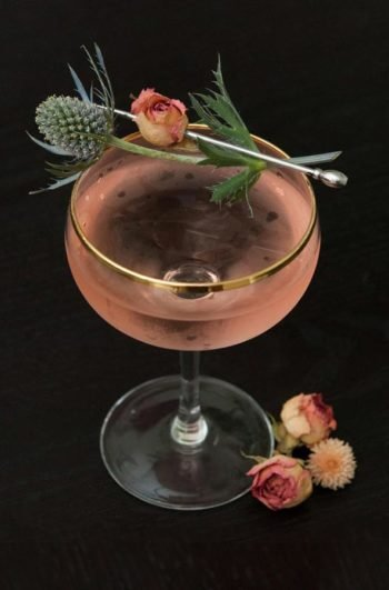 A pink martini, garnished with a dry rose and thistle on a dark table, with 3 flowers at its base.