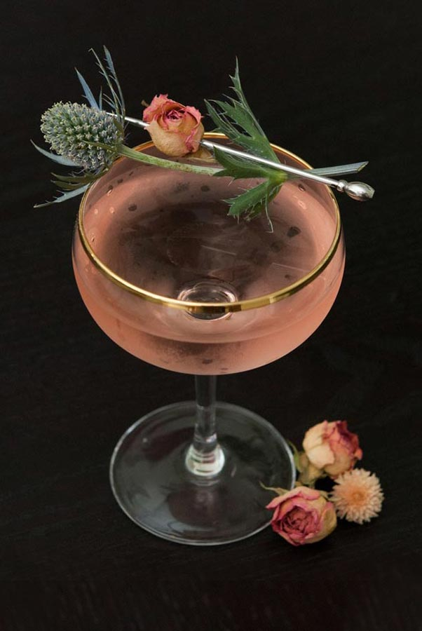 A pink cocktail, garnished with a dry rose and thistle.