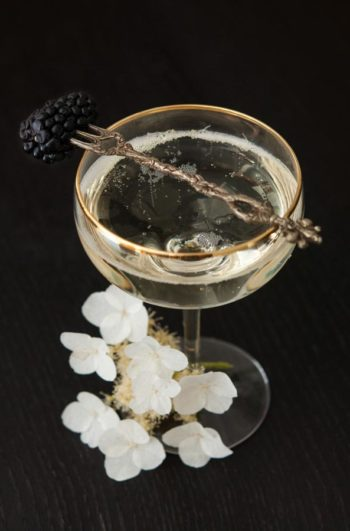 A cocktail, garnished with flowers and a blackberry.