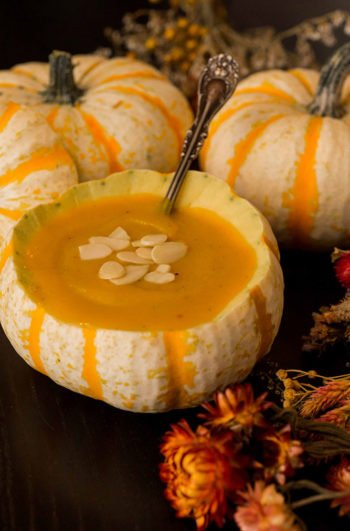 A pumpkin gourd full of soup, garnished with almonds, surrounded by dry flowers and more pumpkin gourds on a black table.
