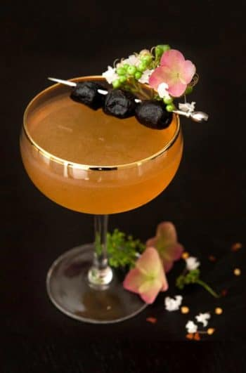 A cocktail garnished with olives and flowers.