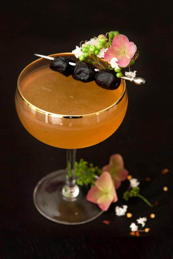 A cocktail on a dark table garnished with olives and flowers, with a few flowers at its base.
