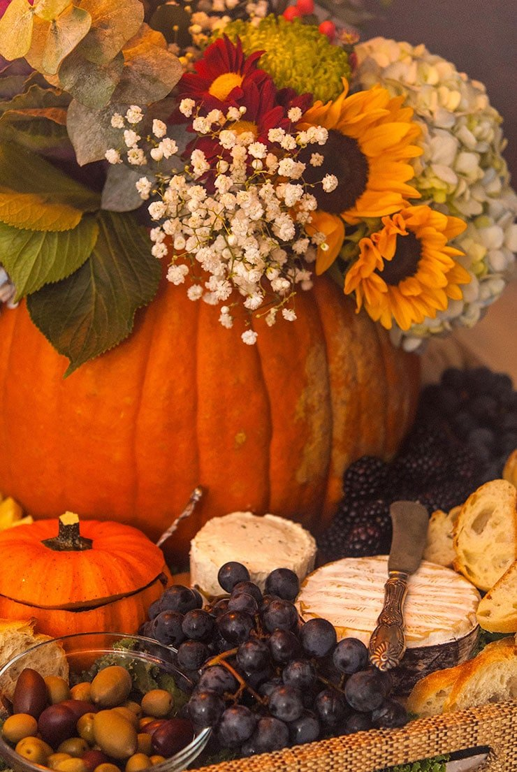 A pumpkin filled with flowers sitting in a tray full of cheese, grapes, bread, and olives with a small pumpkin gourd cut like a bowl.