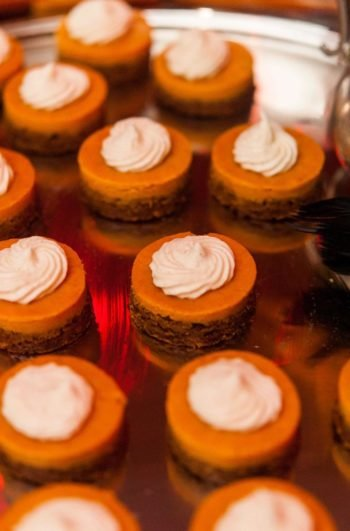 12 mini-pumpkin pies on a silver tray with whipped cream on top.