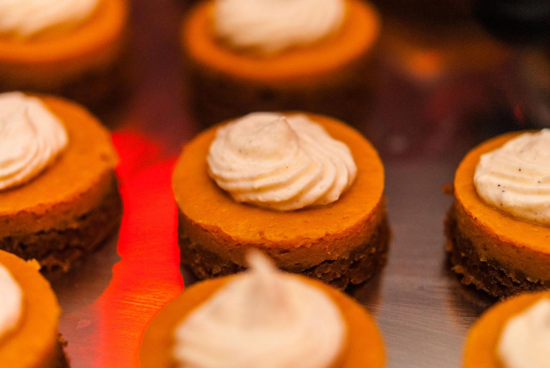 A closeup of 8 mini-pumpkin pies on a silver tray with whipped cream on top.