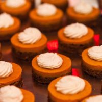 12 small pumpkin pies, topped with whipped cream on a metal tray.