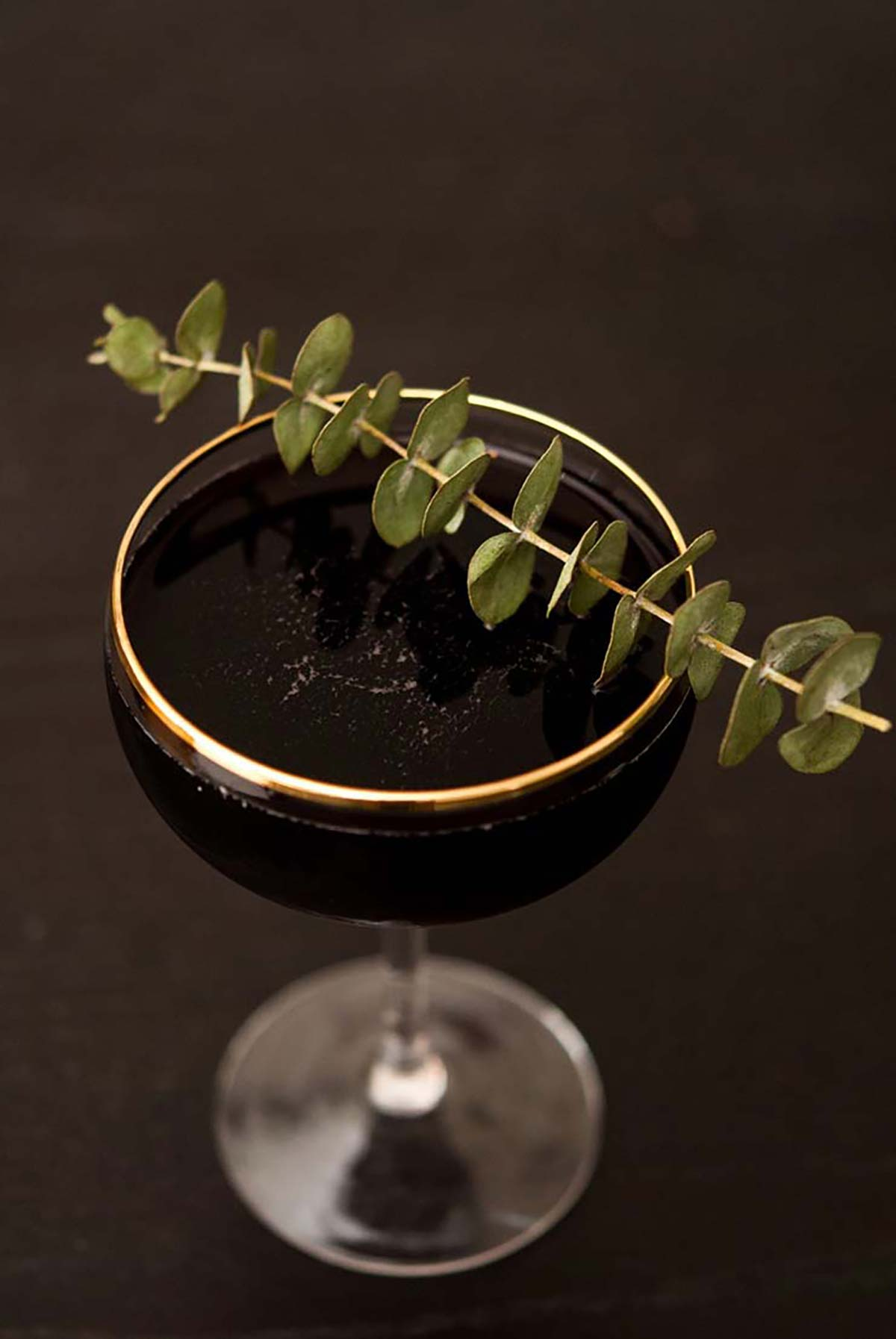 A dark cocktail in a gold rimmed glass, garnished with eucalyptus.