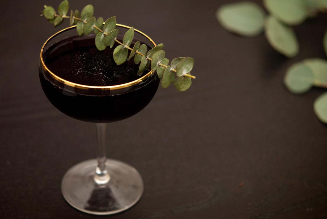 A cocktail in a gold-rimmed glass, garnished with eucalyptus on a dark table.