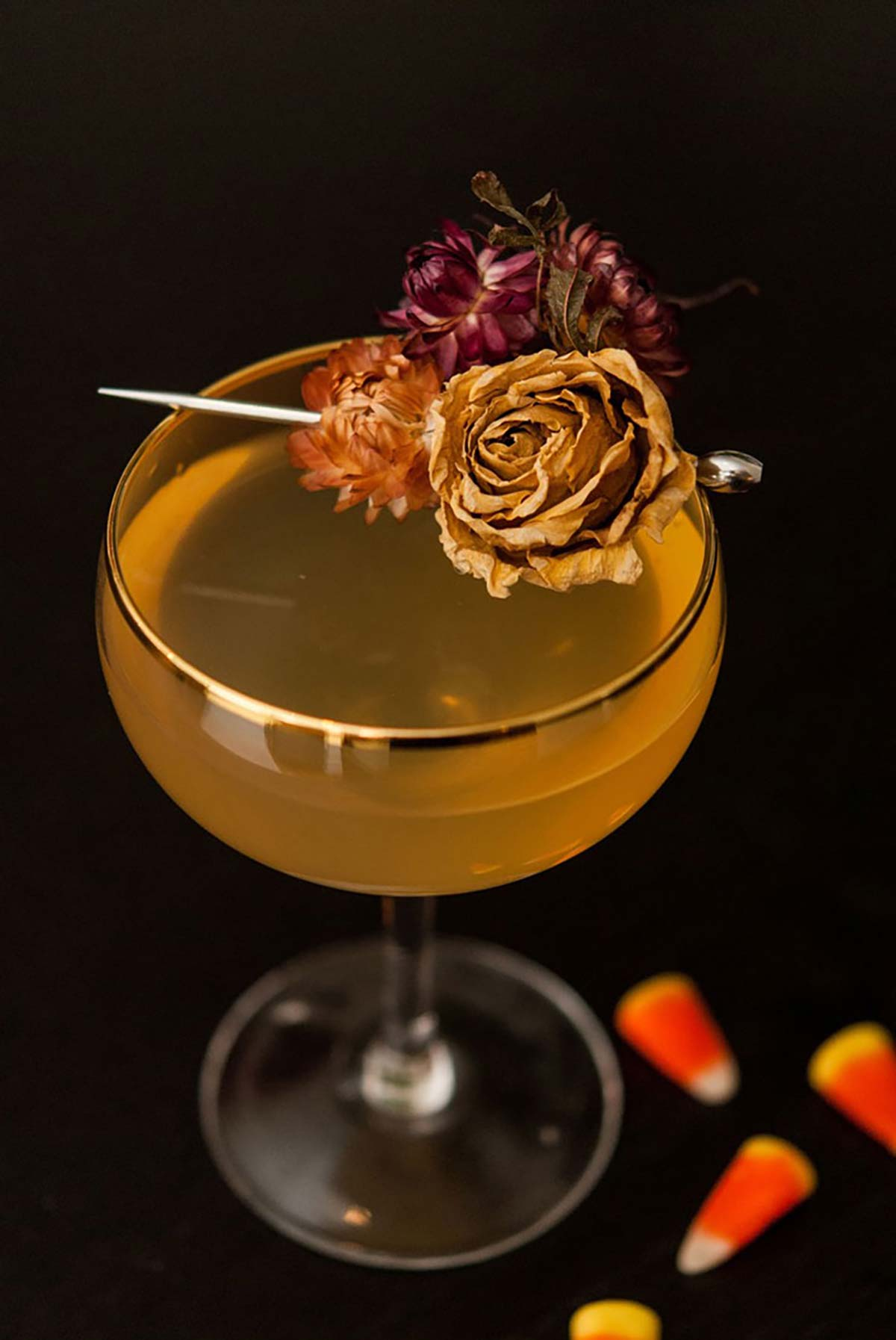A cocktail garnished with dry flowers on a black table sprinkled with 3 candy corns.