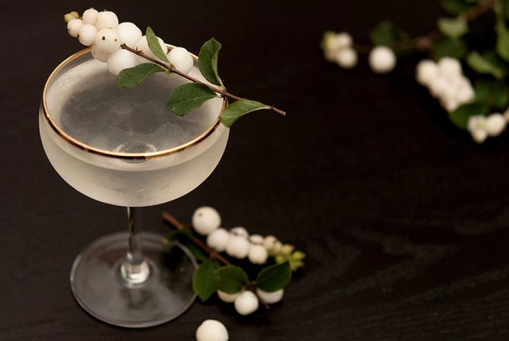 A clear cocktail in a gold-rimmed glass, garnished with white ghost berries on a black table, sprinkled with a few loose ghost berries.