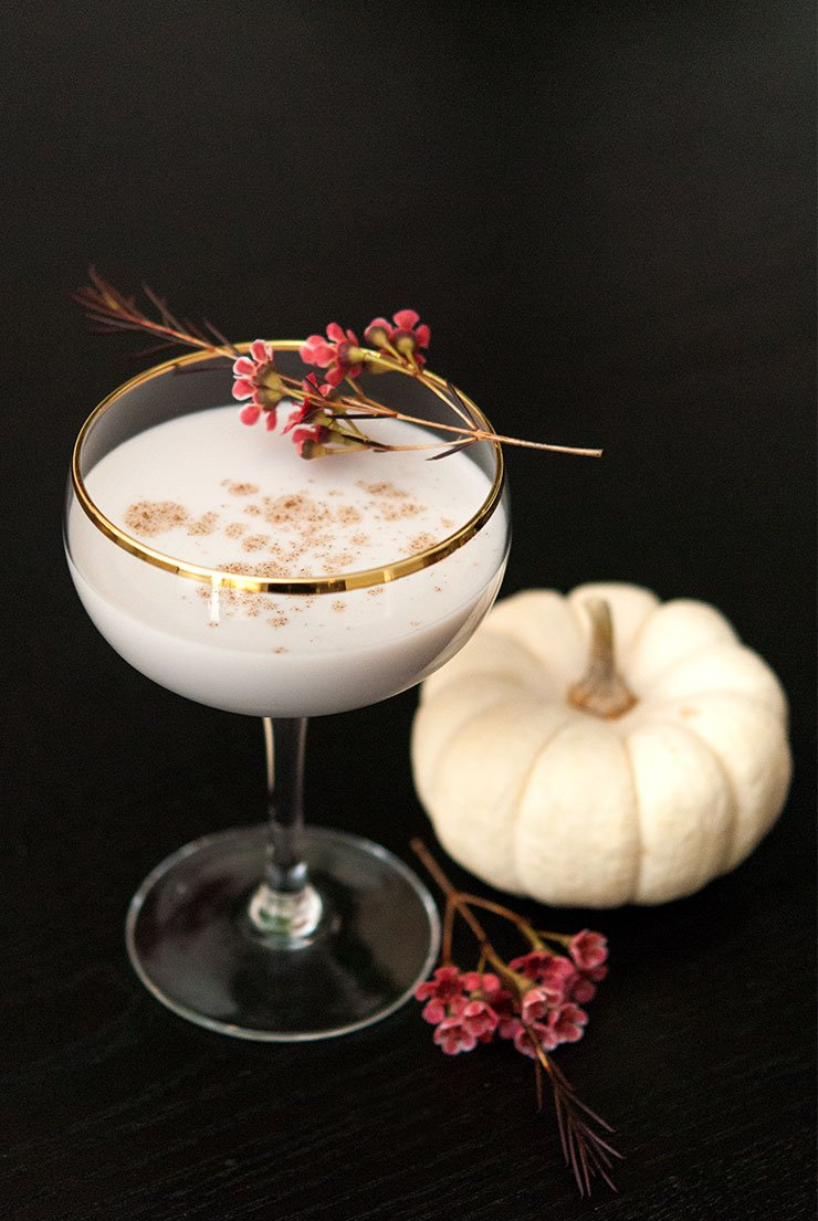 A cocktail with a gold rim, garnished with spice and small flowers with a small pumpkin in the background.