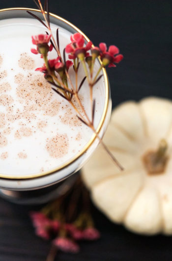 A white cocktail with a gold rim, garnished with spice and small flowers with a white pumpkin in the background.