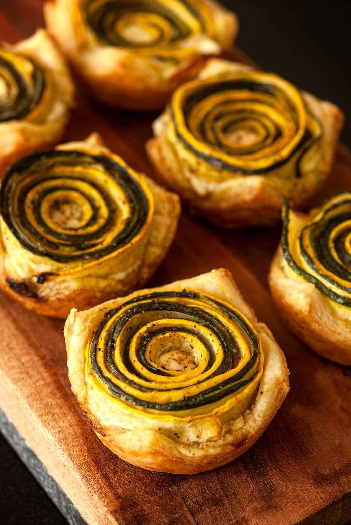 6 pesto zucchini rosettes on a wooden board.