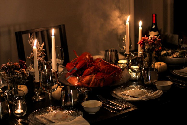 A large bowl of steaming lobsters in teh center of a table, surrounded by plate settings, small white bowls, cutlery, candles and red wine.