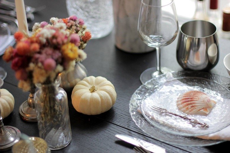 A table setting with tiny white pumpkins, small vases with dry flowers, clear plates, silver cups and a sea shell placed in the center of a plate.
