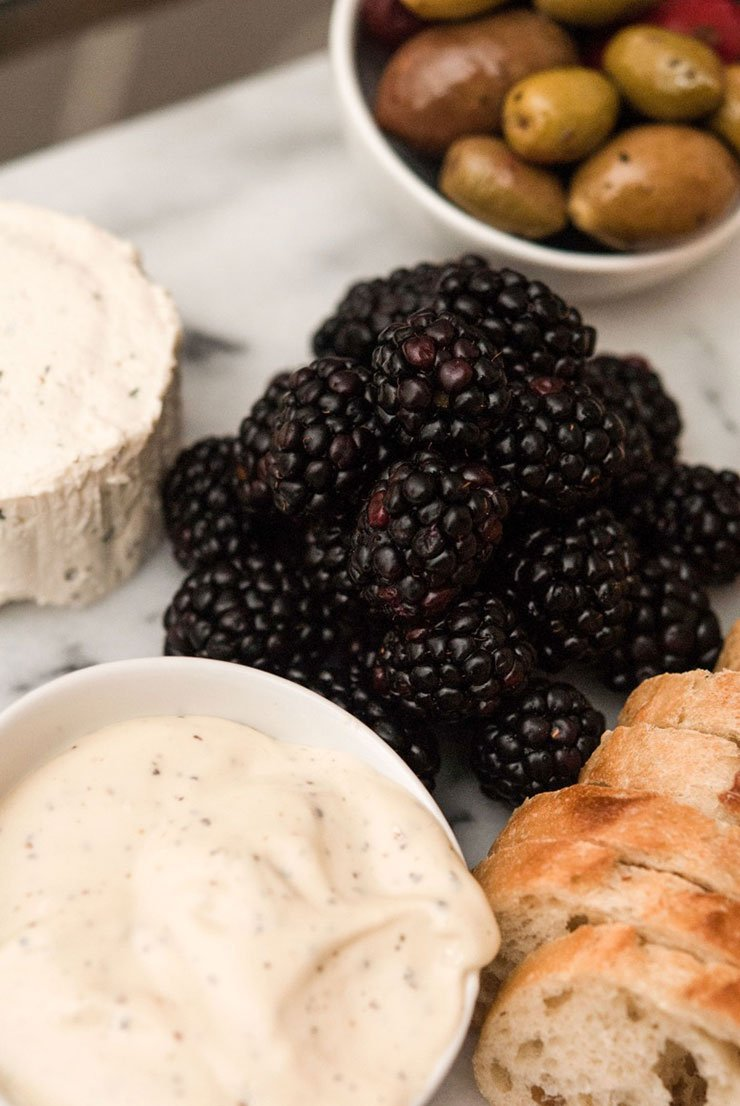 A pile of blackberries on a marble plate surrounded by sliced bread, cheese and a bowl of olives.