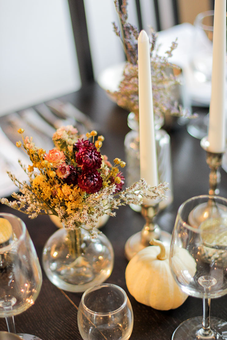 A place setting with white gandles in silver candle sticks, white pumpkins and stemware on a black table.