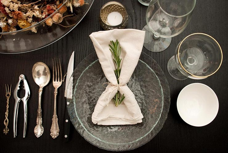 A napkin tied with string, with a sprig of rosemary tucked inside. The napkin is on top of a bowl, on top of a plate surrounded by utensils and glassware.
