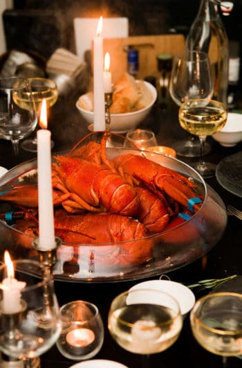 A table with a large bowl of cooked lobsters in the center, surrounded by glasses, candles and cutlery.
