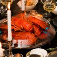 A large bowl with 5 cooked lobsters in the center of a table, set with glasses, candles and bowls of bread.