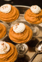 5 small glasses full of pumpkin mousse topped with whipped cream, sitting on a silver tray.