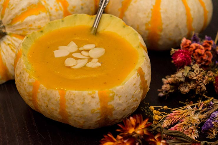 a pumpkin gourd bowl full of soup, garnished with almonds, surrounded by dry flowers and more pumpkin gourds on a black table.