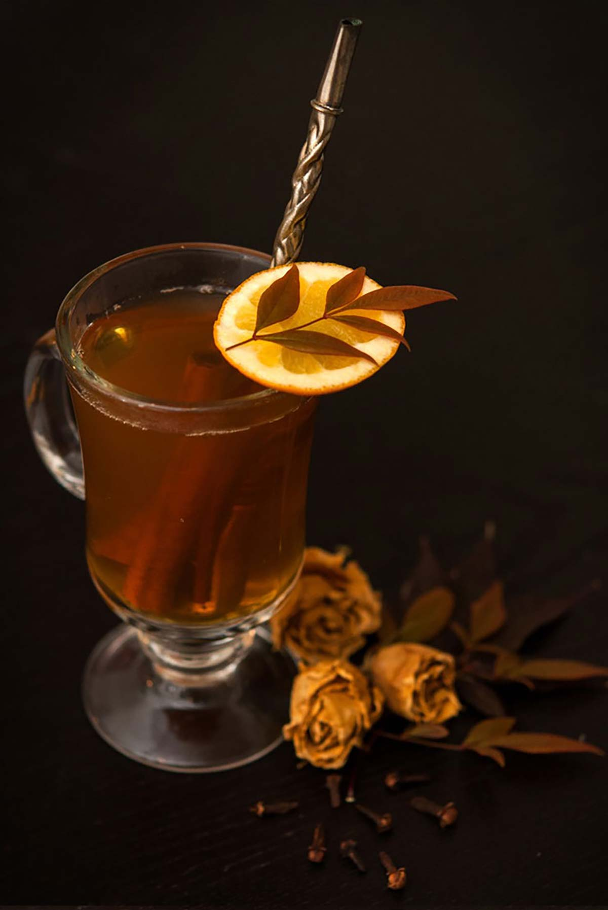 A mug of hot toddy, garnished with an orange slice, topped with a small lead, with a few dry roses and leaves at its base.