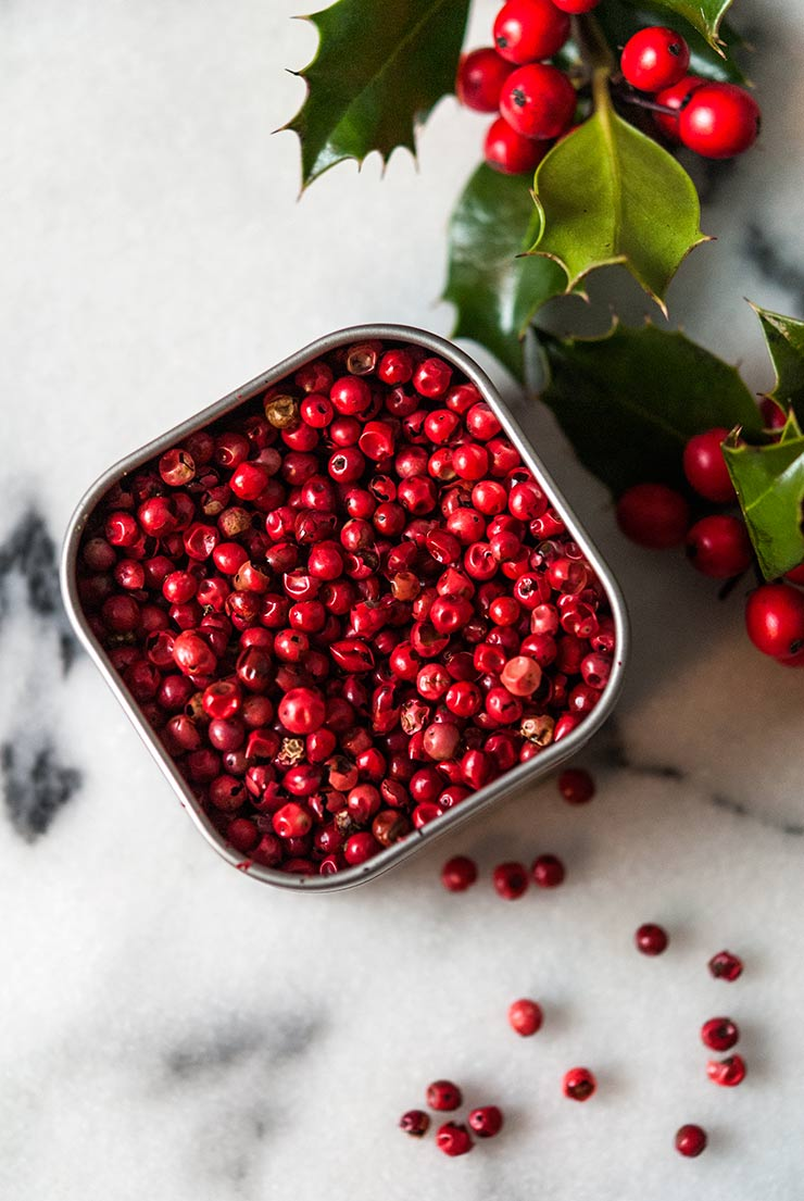 Pink peppercorns on a marble table surrounded by holly.