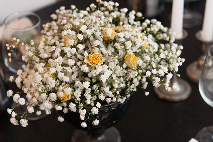 A bouquet with baby's breath and yellow roses on a table.
