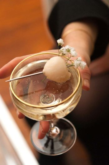 A closeup of a hand holding a cocktail garnished with a lychee and baby's breath.