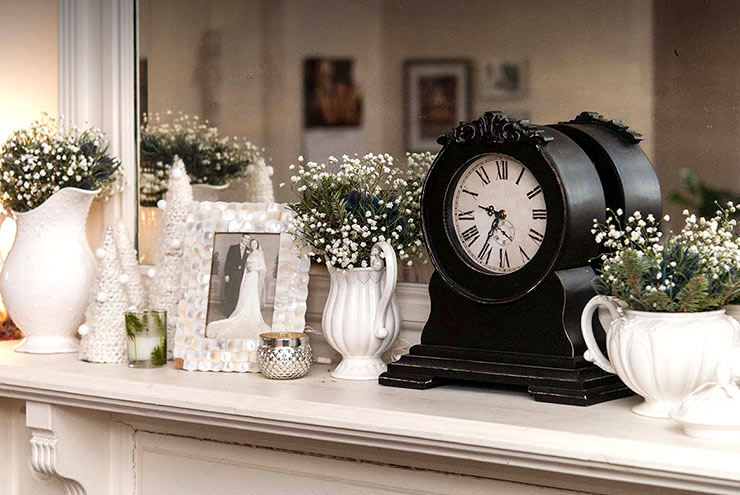 A mantle with a vintage wedding photo, a vintage clock and various vases holding baby's breath and greenery.