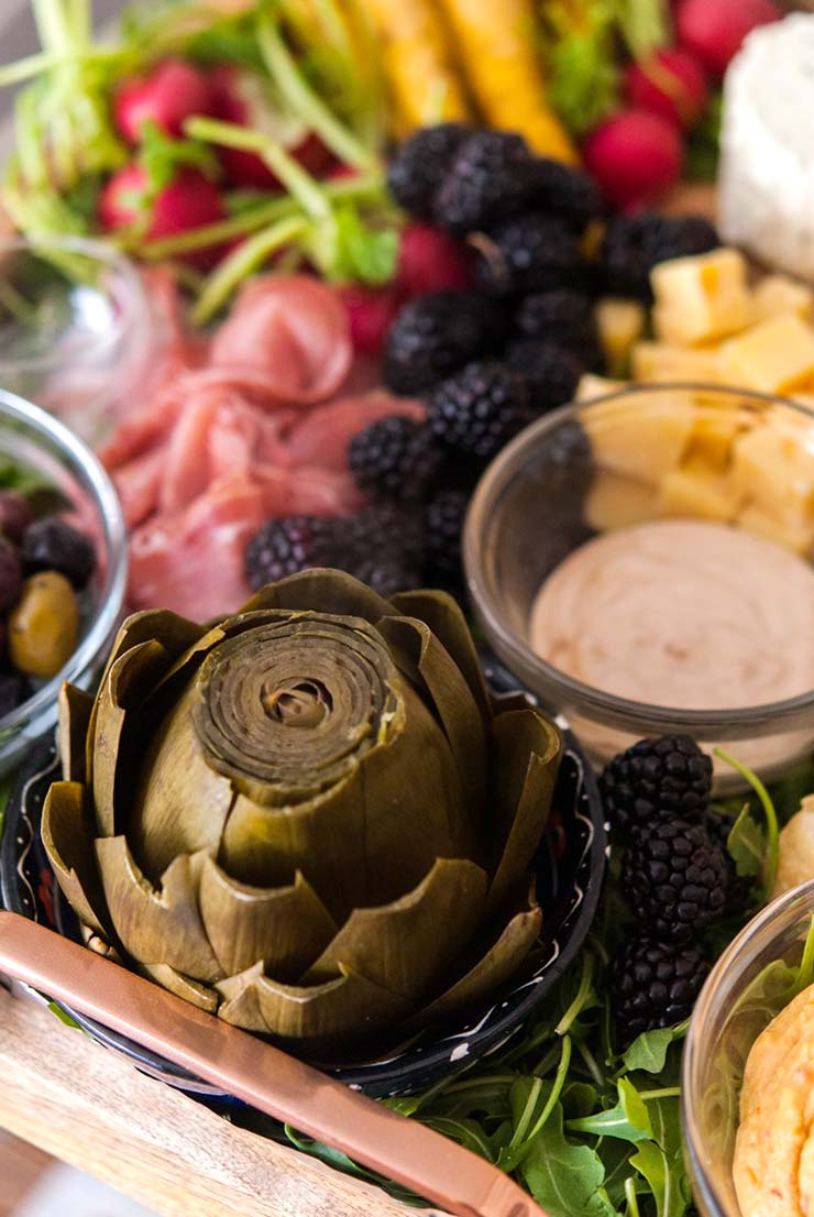 A tray with an artichoke, a bowl with dipping sauce, a bowl with olives, prosciutto, cheese blackberries and radishes.