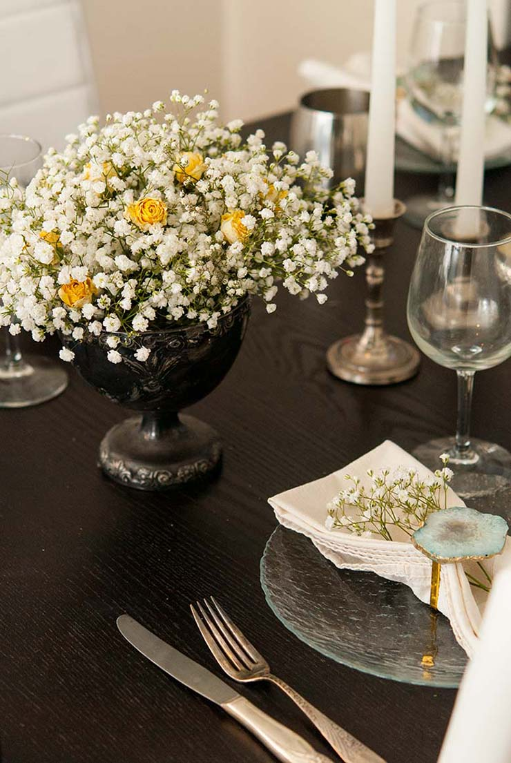 A dining room table set with plates, napkins, glasses, candles and a baby's breath bouquet with yellow roses.