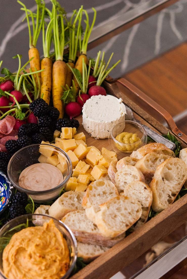 A tray with bread, carrots, prosciutto, cheese, blackberries and radishes.