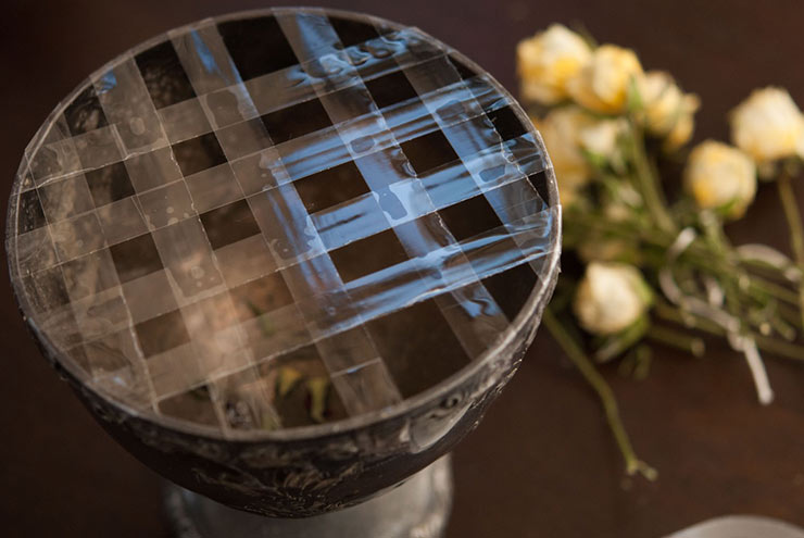 A tarnished silver bowl with tape criss crossed on top to make a grid with yellow roses in the background on a table.
